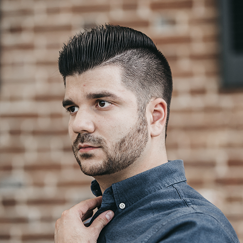 An image of a man with black hair and shot back and sides hairstyle.