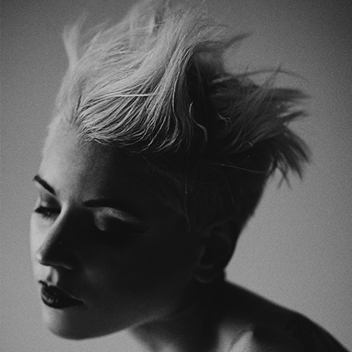 An image of a pretty woman with short blond hair that is in a spiky style.